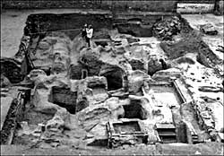 Halifax Place, Nottingham: excavations from 1978 to 1980 revealed a dense concentration of medieval and later structural remains, including post-hole settings interpreted as the foundations of Pre-Conquest bow-sided buildings and a host of medieval to modern caves, pits, wells and building foundations. The photograph shows Gordon Young triangulating the northern edge of a pre-Conquest boundary ditch running from east to west. ©Nottingham City Museums and Galleries.